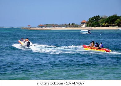 People enjoying water activities on a beach in Bali, Indonesia