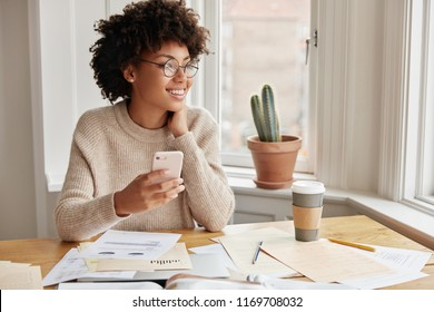 People, ethinicity and entertainment concept. Beautiful delighted thoughtful pleased female financier checks updates for organiser on mobile phone, sits at desk with documents, studies graphics