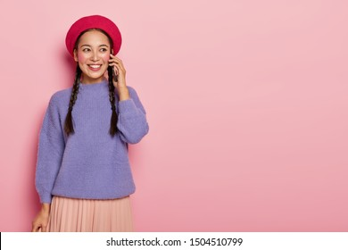 People, ethnicity, communiction concept. Talkative pretty girl with eastern appearance enjoys telephone conversation, holds modern cellular near ear, wears stylish red beret and violet jumper