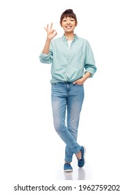 people, ethnicity and gesture concept - happy asian young woman in cotton shirt and jeans showing ok hand sign over white background