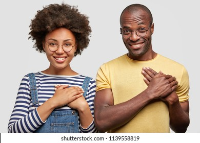 People, ethnicity and gratitude concept. Smiling young African American female and male keep hands on chest, have friendly expressions, isolated over white background, feel thankful to somebody