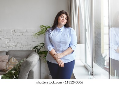 People, excess weight, style and fashion concept. Indoor shot of gorgeous young overweight brunette female wearing large size blue shirt and jeans standing in living room interior by the window