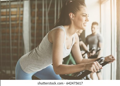 People exercise on stationary bikes in fitness class. People workout in gym. Exercise on elliptical machine. Man personal trainer.