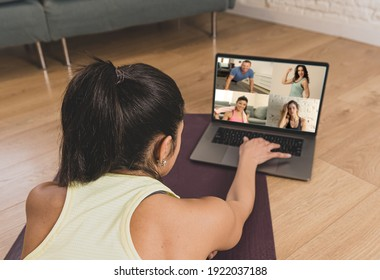 People exercising at home connected to online fitness class on laptop. Woman personal trainer coach on zoom teaching workout exercises in online body care, health and wellness business.