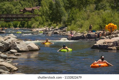 People families having fun cooling off floating in inflatable tubes down the San Juan River during hot summer day in Pagosa Springs, Colorado, USA