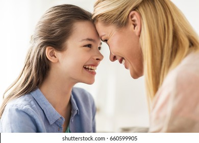 people and family concept - happy smiling girl with mother at home