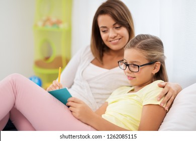 people, family and education concept - happy daughter with mother writing to notebook at home