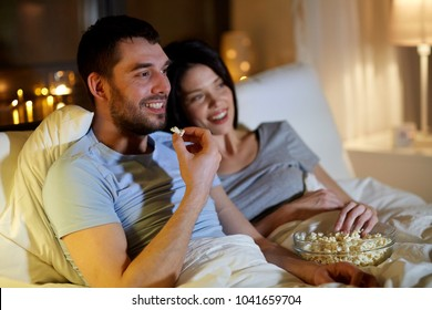 people, family and leisure concept - couple with popcorn watching tv at night at home