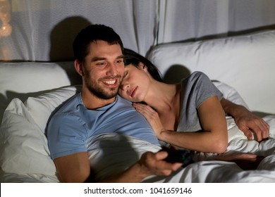 people, family and leisure concept - happy man with remote watching tv in bed at night and woman sleeping