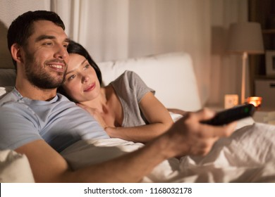 people, family and leisure concept - happy couple watching tv in bed at night at home