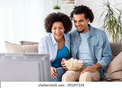 people, family and leisure concept - smiling couple with popcorn watching tv at home