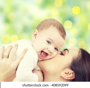 people, family, motherhood and children concept - happy mother hugging adorable baby over green lights background
