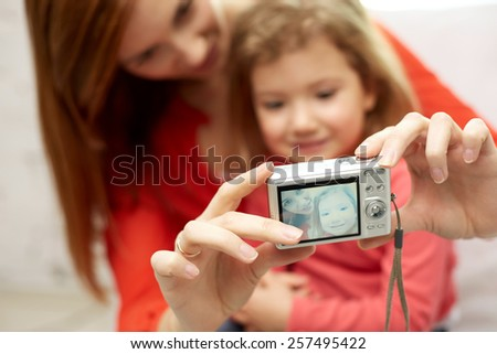 people, family and technology concept - close up of happy mother and little daughter with camera taking selfie