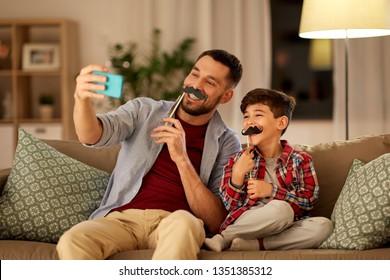 人々、家族、テクノロジーのコンセプト – 幸せな父と子息、口ひげを持つパーティの小道具、スマートフォンで自分で持ち運び、夜に自宅のソファに座る