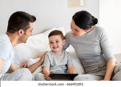 people, family and technology concept - happy mother, father and little boy with tablet pc computer in bed at home or hotel room