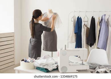 People and fashion concept - Back view of fashion shop owner dressed in stylish outfit measuring materials on mannequin in office
