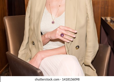 People, fashion, jewelry and luxury concept, closeup of woman wearing luxury jewelry sitting on armchair. Color gemstone ring and pendant with colored diamonds and gemstones