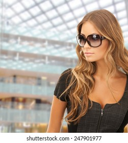 people, fashion, shopping and consumerism concept - beautiful young woman in shades over mall background