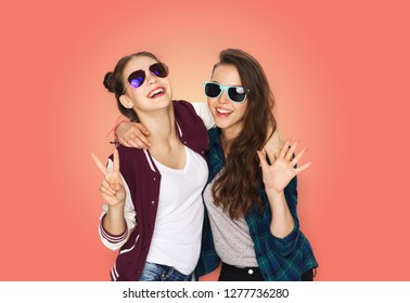 people, fashion and summer concept - happy smiling pretty teenage girls in sunglasses showing peace hand sign over living coral background