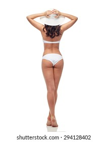 people, fashion, swimwear, summer beach and beauty concept - young woman in white bikini swimsuit from back