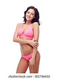 people, fashion, swimwear, summer and beach concept - happy young woman posing in pink bikini swimsuit