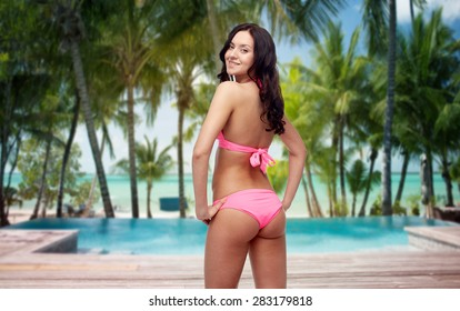 people, fashion, swimwear, summer and travel concept - happy young woman in pink bikini swimsuit looking back over tropical beach with swimming pool background