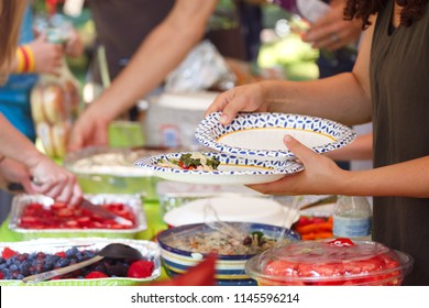 People filling plates at a summer cookout