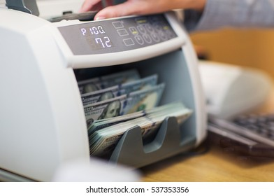 people, finance and cash concept - clerk hand counting dollars with electronic money counter machine at bank office or currency exchanger