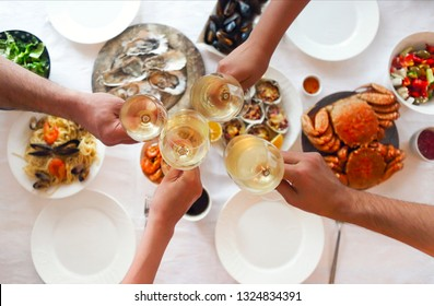 People fine dining seafood and white wine on the table. Top view
