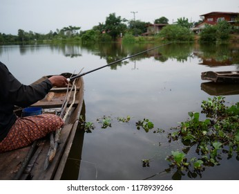 people fishing in the canal with fishhook.