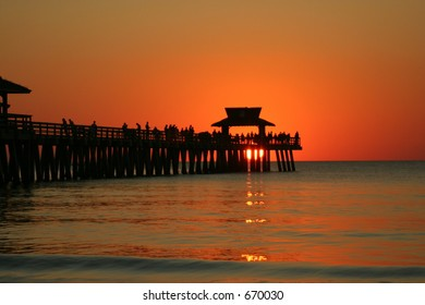 People fishing at naples pier during sunset