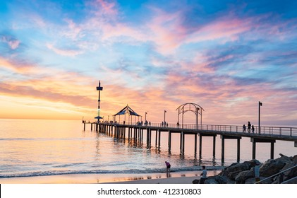 People are fishing on the Brighton Beach Jetty at beautiful sunset.