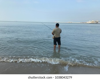 People fishing at sea shores by using fishing rod.