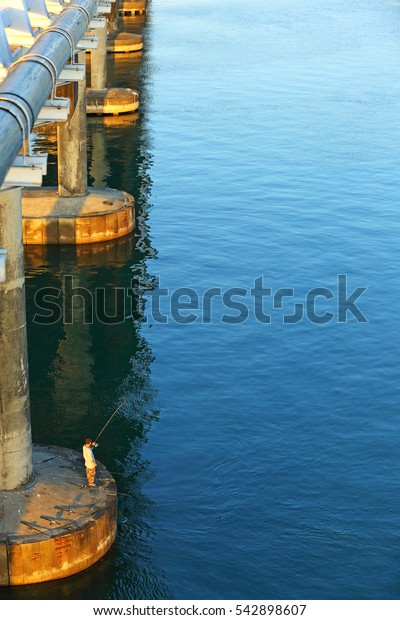 People are fishing under the cross bridge on sea in the morning