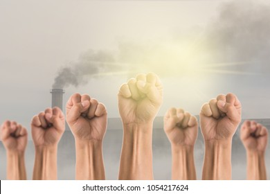 People Fists raised fighting for protest over the Smokestack Factory with black smoke on the sky with cloud and sun background