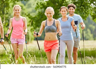 People in fitness course nordic walking in the nature