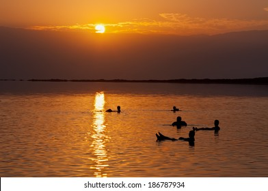 People floating at the Dead sea at dawn, Israel . The Dead Sea is a salt lake in Israel. Its shores are the lowest point on the surface of the Earth on dry land.