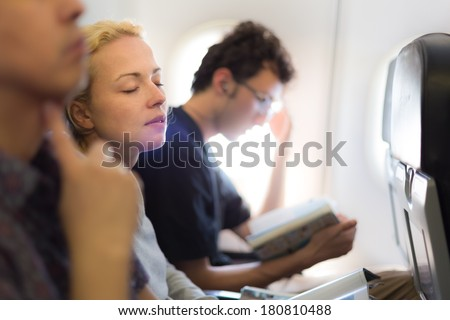 People flying by plane. Interior of airplane with passengers killing time on their seats.