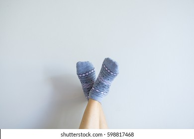 people foot wearing cute grey socks on the wall