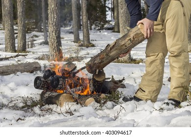 People in the forest casts a log in a campfire