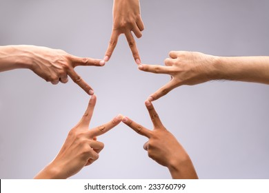 People forming star shape with their fingers