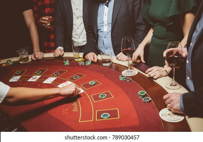 People / friends play poker roulette at the table in the casino. A group of young people at a roulette table with a tape measure. Table for gambling in a luxury casino. Vintage photo processing