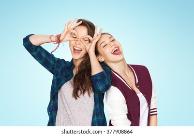 people, friends, teens and friendship concept - happy smiling pretty teenage girls having fun and making faces over blue background