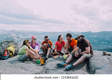 People friendship hangout traveling destination camping concept. Group of six hungry hikers travelers in sportswear relaxing and having snacks after hiking at top of mountain. View with dramatic sky.
