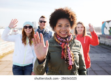 people, friendship and international concept - happy african american young woman or teenage girl in front of her friends waving hands on city street