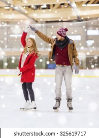 people, friendship, sport and leisure concept - happy couple holding hands on skating rink