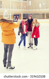 people, friendship, technology and leisure concept - happy friends taking photo with tablet pc on skating rink