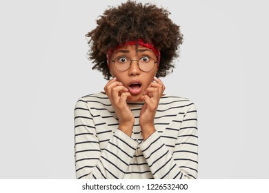 People, fright concept. Scared Afro American model gestures with anxious expression, horrified to see something horrible near, has bated breath, dressed in casual outfit, stands indoor over white wall