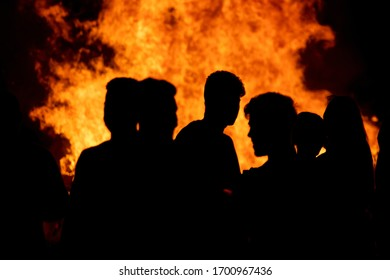 People in front of a bonfire at night during San Juan festivities in Spain