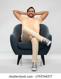 people and furniture concept - happy smiling young indian man sitting in chair over grey background